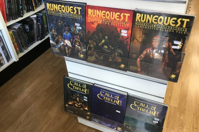 Covers for various RuneQuest and Call of Cthulhu RPG books on display in a game store.