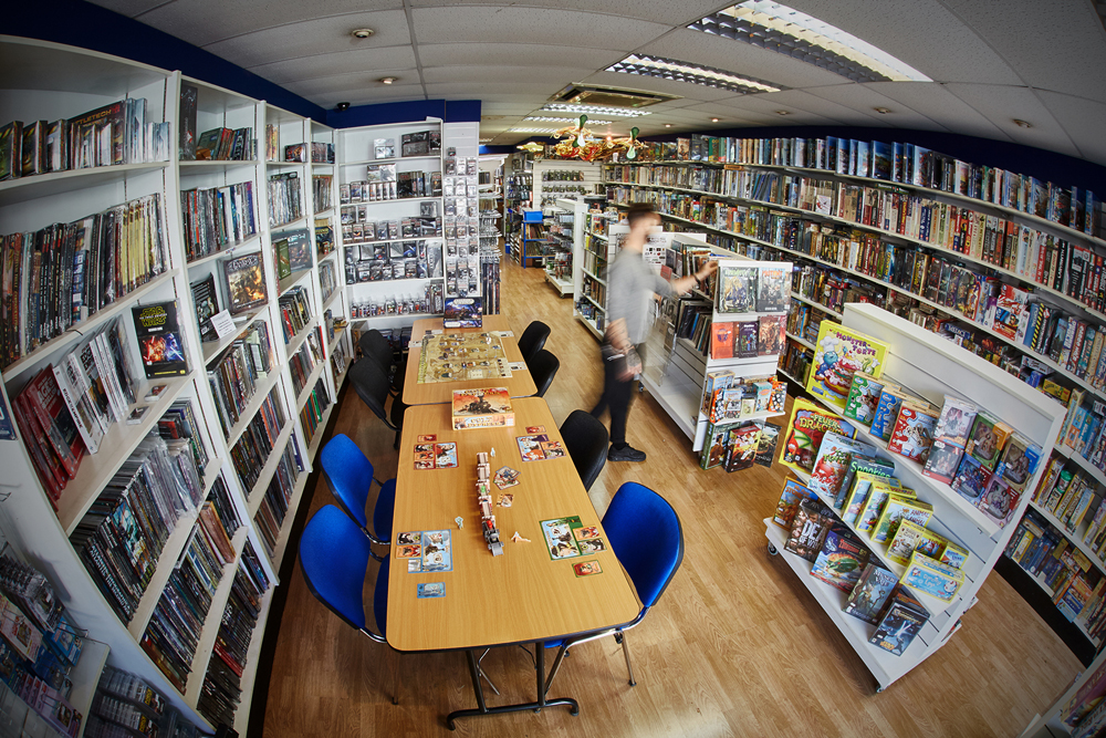 A fish-eyed photograph of a hobby shop, with boardgames set out on the table, and the blurred figure of a shopper picking out a game book.
